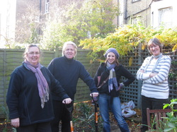 Group of Transition Town members at the plant and rant holding spades in a garden